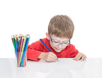 The five-year-old boy in blue points sits at a white table and and draws pencils Royalty Free Stock Photography