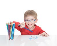 The five-year-old boy in blue points sits at a white table and and draws pencils Stock Photo