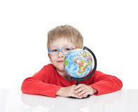 The five-year-old boy in blue points sits at a white table and holds the globe in hand Royalty Free Stock Photo