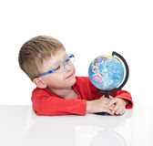 The five-year-old boy in blue points sits at a white table and holds the globe in hand Royalty Free Stock Photography