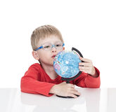 The five-year-old boy in blue points sits at a white table and holds the globe in hand. Isolated on a white background Stock Image