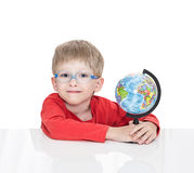 The five-year-old boy in blue points sits at a white table and holds the globe Stock Photography