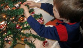 Five-year-old Boy Decorating Christmas Tree royalty free stock photos