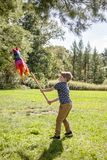Boy hitting a pinata at outside birthday party royalty free stock photo