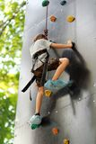 Five year old boy learning to climb the rock wall outside in the summer park. Bouldering Stock Photography