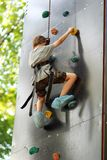 Five year old boy learning to climb the rock wall outside in the summer park. Stock Photography
