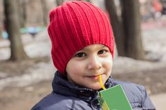 The child drinks juice in the Playground. emotional close-up portrait. royalty free stock photography