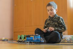 Five year old boy playing on the floor by rail. Little boy playing with railway lying on the floor royalty free stock image