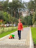 Five year old boy pulling a bright colorful truck among greenery in the park. Candid portrait Stock Photography