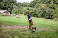 Five year old boy running outside on farm. Happy five year old boy wearing running and playing outside on a farm royalty free stock photo