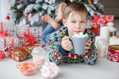A 5 year old boy lies next to a beautiful Christmas tree holding a large cup of coffee with marshmallows. Five year old boy with short hair,dressed in a bright Royalty Free Stock Photos