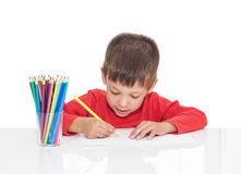 The five-year-old boy sits at a white table and draws pencils. Isolated on a white background Stock Photos
