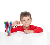 The five-year-old boy sits at a white table and draws pencils Stock Images