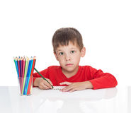The five-year-old boy sits at a white table. And draws pencils, isolated on a white background Royalty Free Stock Photography