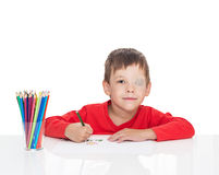 The five-year-old boy sits at a white table and draws pencils, the left eye is stuck with a plaster. Sight vision stimulation, treatment, load of the right eye Stock Images