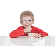 The five-year-old boy sits at a white table and eats yogurt Stock Photos