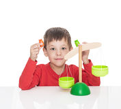 The five-year-old boy sits at a white table and plays with wooden scales Stock Photo