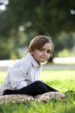 Five year old boy sitting on blanket in park Stock Photo