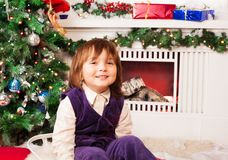 Five year old boy sitting by Christmas tree Stock Photo