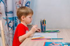 Five-year-old child draws with colored pencils Royalty Free Stock Photos