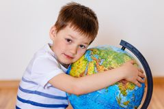 Five-year-old child embracing large globe royalty free stock photo