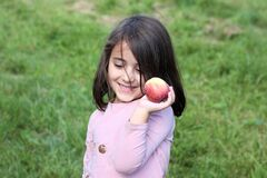 Happy little girl with an apple