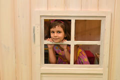 The five-year-old girl looks out in a lodge window. Kindergarten Royalty Free Stock Image