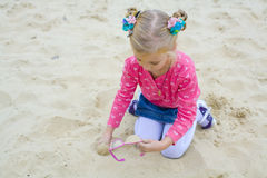 Five-year-old girl plays on a beach Stock Images