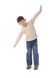 Five year old imitating flying smiling. Five year old little boy imitating flying as an airplane, smiling stock photos