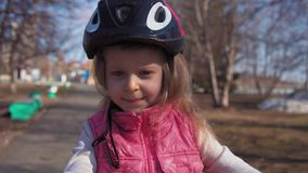 Five-year-old little blonde girl riding bike in an old park. stock footage