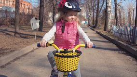 Five-year-old little blonde girl riding bike in an old park. stock video
