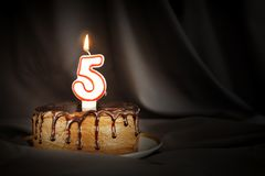 Five years anniversary. Birthday chocolate cake with white burning candle in the form of number Five. Dark background with black cloth stock photos