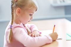 Five years old  blonde girl sitting at classroom and writing. Cute five years old  blonde girl sitting at classroom and writing Royalty Free Stock Images