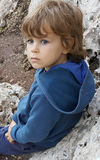 Five years old boy, unhappy look, blue eyes, sitting outdoor on Stock Image