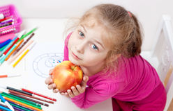 Five years old caucasian blond child girl with apple Royalty Free Stock Images