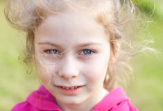 Five years old caucasian blond child girl. Portrait of five years old caucasian blond child girl standing outdoor surrounded by green grass background on a windy royalty free stock photography