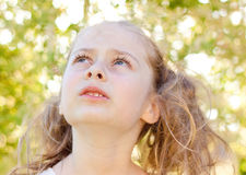 Five years old caucasian child girl in the garden looking up Royalty Free Stock Image