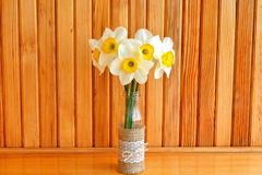 Five yellow daffodils in a vase. Wooden background Stock Images