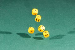 Five yellow dices falling on a green table. Five yellow dices falling on a isolated green table stock photography