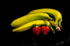 Five yellow and green banana`s and two strawberry`s. Fruits of four different banana cultivars Royalty Free Stock Image