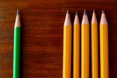 Five yellow pencils and one green pencil Royalty Free Stock Photos