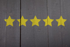 Five yellow ranking stars on wooden background Stock Photo