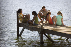 Five young adults relaxing at edge of lake jetty Royalty Free Stock Images