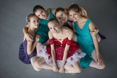 Five young ballerinas sitting on the floor and looking to the ca Royalty Free Stock Images
