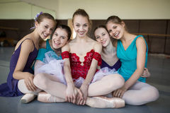 Five young ballerinas sitting on the floor Royalty Free Stock Image
