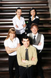 Five young business people are standing as a team Royalty Free Stock Images