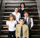 Five young business people are standing as a team Stock Photos