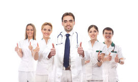 Five young Caucasian medical workers together. Five young and smart Caucasian medical workers in white clothes standing together and holding thumbs up as a sign Stock Image