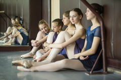 Five young dancers in the same dance costumes, resting sitting o Royalty Free Stock Photos