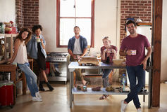 Five young friends having coffee in kitchen look to camera Stock Image